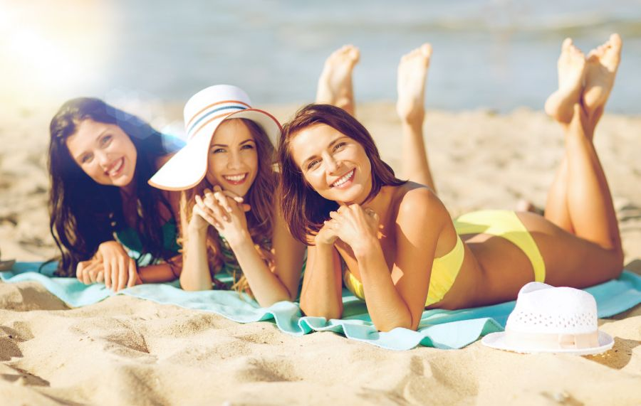 tri ženy sa opaľujú na pláži